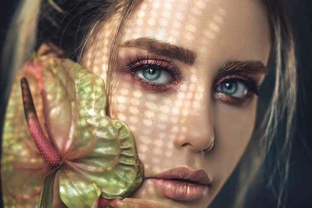 mulher olhando para a foto com longos cílios após procedimento de lash design